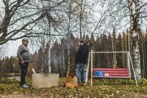 Kaksi miestä seisoo kaivorenkaan vieressä, missä savuaa.