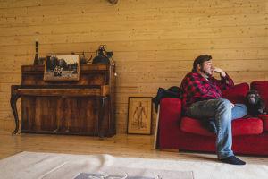 Mies flanellipaidassa istuu punaisella sohvalla, katselee poispäin.