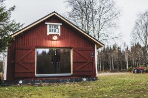 Mies flanellipaidassa seisoo ison ikkunan takan ja katselee ulos punaisesta ladosta.