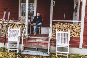 Mies istuu tuolilla talon kuistilla. Edessä halkopuita ja parit sukset.