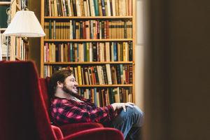 Mies istuu nojatuolissa hymyillen. Takana kirjahylly.