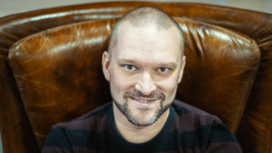 Isyyspakkaus-bloggaaja Tommi Koivisto istuu ruskeassa nahkatuolissa, katsoo suoraan kameraan ja hymyilee.