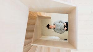 Valeäiti-bloggaaja Hanne Kettunen makaa portaikon alapäässä. Kuva otettu kierreportaiden yläpäästä.