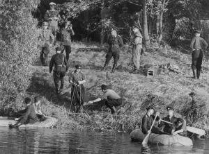 En svartvit bild från 1960-talet med uniformsklädd män på en strandbank och i vattnet i två gummibåtsliknande farkoster sitter totalt fyra män och paddlar i väg från stranden.