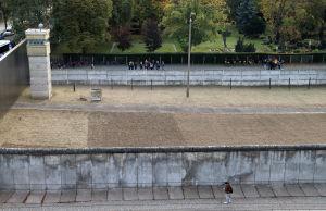 En bred stenmur fotograferad uppifrån. På bägge sidor finns människor som tittar på muren.