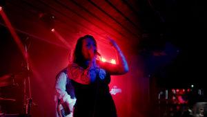Nuusa Niskala laulaa lavalla punaisissa kohdevaloissa.