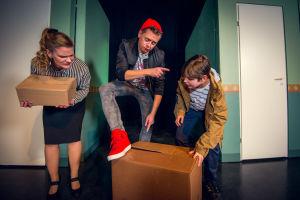 En man håller ena foten på en papplåda på golvet. Bredvid en pojke som håller ena handen på lådan. På andra sidan av mannen en kvinna som lutar sig framåt och håller en mindre papplåda i händerna.