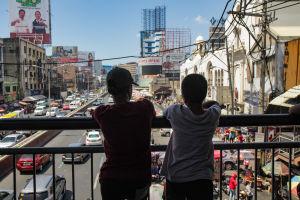 Kaksi lasta seisoo sillalla ja katsoo liikennettä sillan alapuolella.