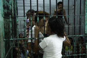 Nainen vierailulla vankilassa, katsomassa sellissä olevaa miestä