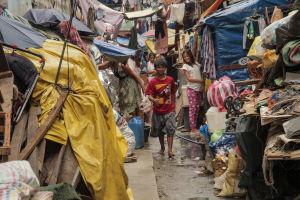 Nuori poika kävelee kameraa kohti Manilan slummissa