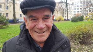En äldre man i blå jacka och blå skärmmössa ler och tittar in i kameran. Han står i en park där träden är utan löv, men på en del buskar finns gröna eller gula löv och gräsmattan är grön.