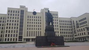 Ett stort vitt hus i flera våningar syns i bakgrunden bakom en mörk staty med en man som står vid ett podium.