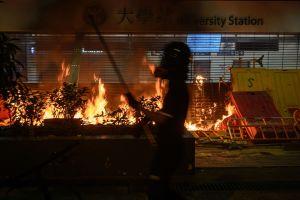 Person står vid en brinnande metrostation i Hongkong.