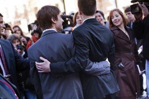 Miespari kädet toistensa vyötäröllä kuvattuna takaapäin