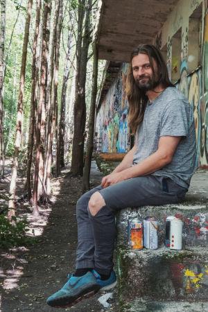 Långhårig man sitter på gammal tågperrong omgärdad av träd som växer mellan tågspåren. Väggarna täckta av graffiti.