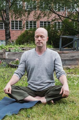 Skallig man sitter i lotusställning på gräsmatta. I bakgrunden en rödtegelbyggnad och en scen av gamla bräder.