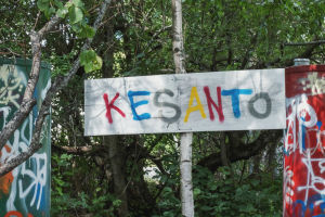 """Skylt med texten """"Kesanto"""" skriven med färggranna bokstäver. I bakgrunden lövträd."""
