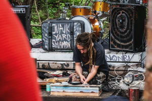 """Rastatukkainen mies soittaa itse rakentamaansa soitinta kyykyssä esiintymislavalla. Taustalla matkalaukku, jonka kyljessä teksti """"Junkyard shaman""""."""