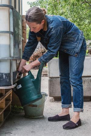 Farkkuasuinen nainen valuttaa ison vesikanisterin hanasta vettä vihreään kastelukannuun.