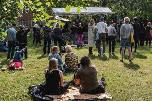 Ihmisiä istuskelee nurmikolla, seisoo ryhmissä kuuntelemassa bändiä, joka soittaa väliaikaisella esiintymislavalla.