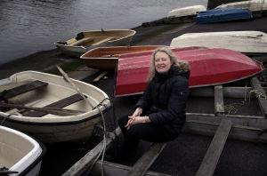Jessica Haapkylä istuu vedestä ylös nostettujen veneiden keskellä laiturilla.