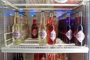 Läskflaskor på en kylskåpshylla.