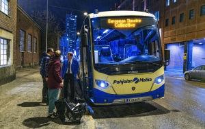 Miehet seisovat bussin vieressä.