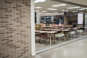 En glasvägg, genom den syns stolar och bord i en skolmatsal