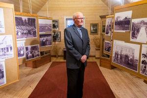 En äldre man poserar i ett fotomuseum