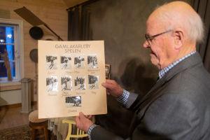 En äldre man håller upp ett plakat med foton på skidåkare.