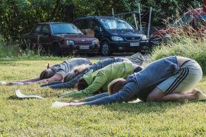 Neljä ihmistä nurmikolla joogamatoilla polvillaan, kädet ojennettuina eteenpäin kohti maton reunaa. Taustalla autoja parkkipaikalla.