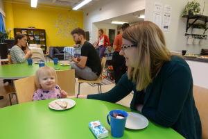 Marika Blomqvist sitter vid kaffebordet och äter mellanmål med dottern Olivia på öppna daghemmet Tallen på Drumsö i Helsingfors.