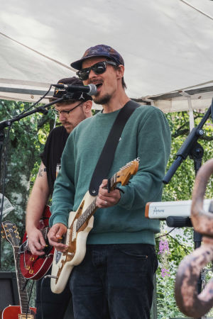 Två män spelar gitarr på en utomhusscen, den ene sjunger i en mikrofon.