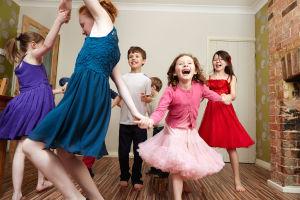 Juhlapukeutuneet lapset tanssivat käsi kädessä piirissä