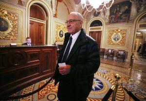 En man i kostym och mörk rock, Alan Derschowitz, traskar in i amerikanska senatens guldprydda entréhall.