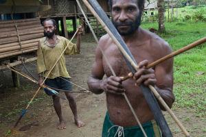 Kaksi jousipysyyin aseistautunutta miestä kylän talojen edustalla