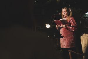 Rosanna Fellman läser ur en bok på en scen.