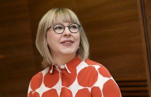 En kvinna med blond page och svartbågade glaögon.