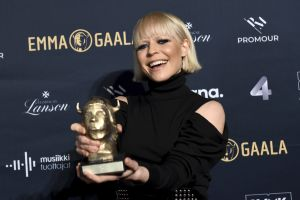En blond kvinna visar upp en guldstatyett.