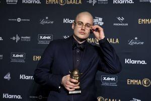 En skallig man i glasögon håller en guldstatyett i handen.