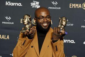 En man i skägg och glasögon håller i två gyllene statyetter.