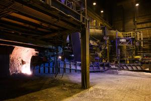 Masugnen inuti, en mörk fabrikshall där det lyser orange av flytande järn där det rinner ut ur masugnen.