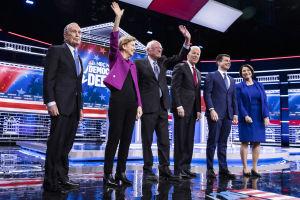 De demokratiska kandidaterna, fyra män i kostym, en kvinna i byxdress och en i blå klänning, står i en tv-studio.
