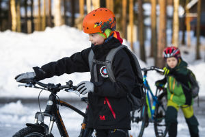 Två barn i vinterkläder och cykelhjälm leder sina cyklar över en snöig skolgård.
