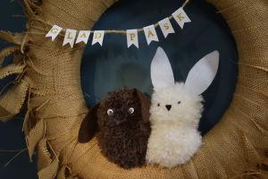 """två kaniner gjorda av garnbollar sitter i en krans med textvimpel där det står """"glad påsk"""""""