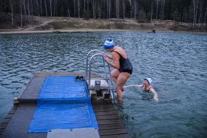 En kvinna står på stege vid en brygga och den andra simmar mot bryggan