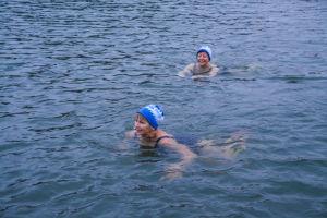 Två kvinnor med mössor på huvudet simmar