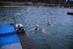 Två kvinnor i mössa simmar mot brygga