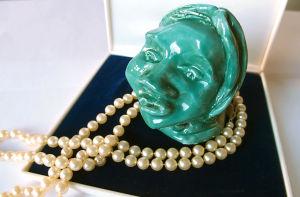 Ett grön skulptur föreställande ett kvinnohuvud med ett pärlhalsband i ett smyckeskrin.