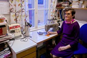 En kvinna sitter vid ett bord med två symaskiner.
